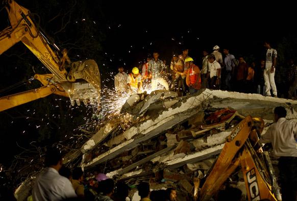 मुंबई के ठाणे में बहुमंजिली इमारत के गिरने के बाद मलबे में दबे लोगों की खोजबीन करते राहत दल के कर्मी।