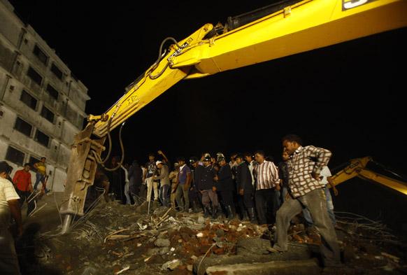 मुंबई के ठाणे में रिहायसी बहुमंजिली इमारत के गिरने के बाद मलबे को हटाती जेसीबी मशीन।