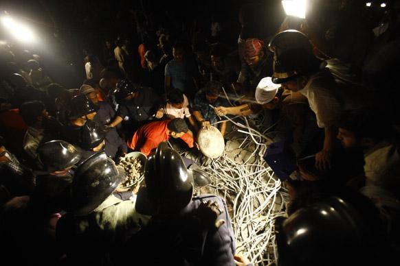 मुंबई के ठाणे में बहुमंजिली इमारत के गिरने के बाद मलबे में दबे लोगों को निकालते राहत दल के कर्मी।