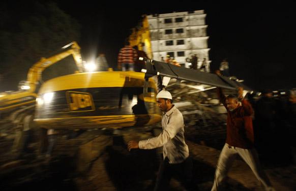 मुंबई के ठाणे में बहुमंजिली इमारत के गिरने के बाद घटनास्थल पर राहत कार्य में जुटे राहत दल के कर्मचारी।