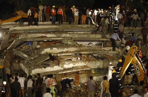 मुंबई के ठाणे में बहुमंजिली इमारत के गिरने के बाद राहत कार्य में जुटे बचाव व राहत दल के कर्मचारी। इस हादसे में अब तक 72 लोगों की मौत हो चुकी है।