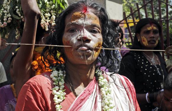 कोलकाता से 55 किमी. दूर बंडेल में एक धार्मिक समारोह में लोहे की छड़ को अपने गालों में घुसाकर भक्ति भाव दर्शाती एक महिला श्रद्धालु।
