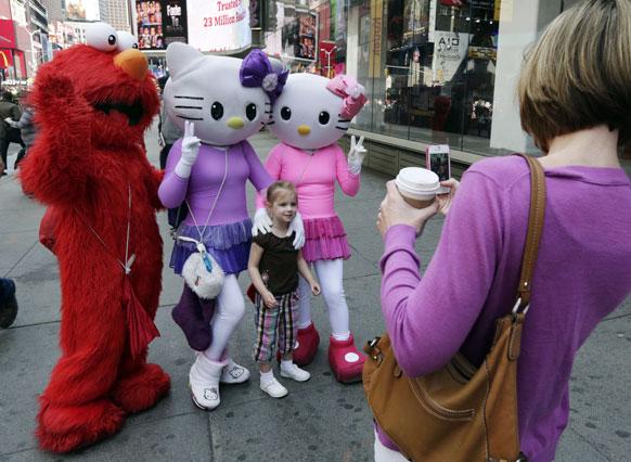 न्यूयॉर्क टाइम्स स्कॉयर में एक छोटी बच्ची के साथ एल्मो और दो हेल्लो किट्टी के किरदार फोटोशूट के लिए पोज देते हुए।