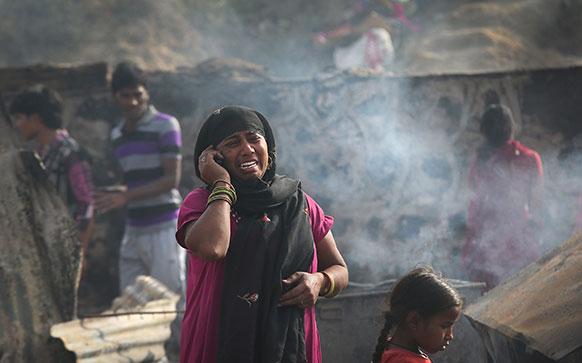 नई दिल्ली में घर में आग लगने से सबकुछ स्वाहा होने से रोती महिला।