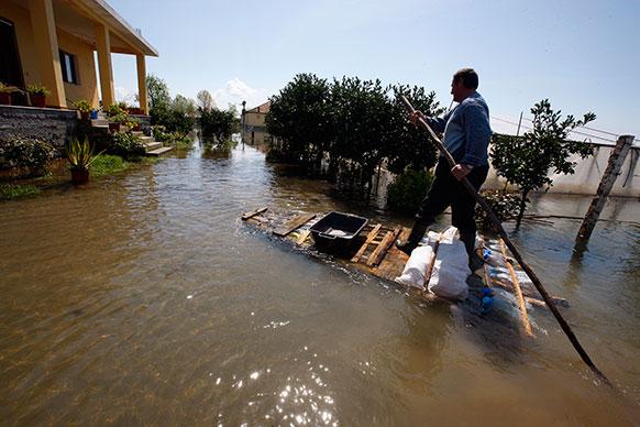 तिराना के 120 किलोमीटर दूर शकोडर शहर में आई बाढ़ से बेहाल लोग।