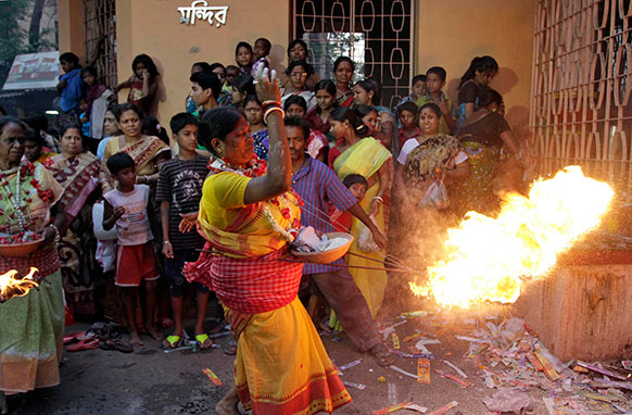 कोलकाता में शिव गजन हिंदू पर्व के दौरान भक्त शिव भगवान के मंदिर के सामने आग से पूजा का करते हुए।