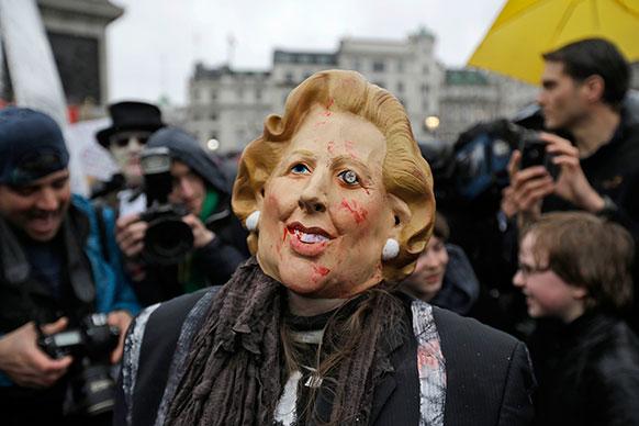 लंदन में ब्रिटेन के पूर्व प्रधानमंत्री मार्गेट थैचर का मास्क पहने प्रदर्शनकारी।