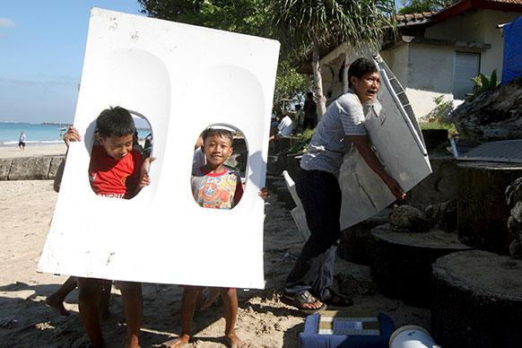 इंडोनेशिया के बाली में जिंबारन बिच के दुर्घटनाग्रस्त विमान के टुकड़े को ले जाते हुए बच्चे।