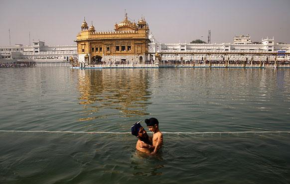 अमृतसर में बैसाखी पर्व के दौरान एक सिख अपने बच्चे के साथ स्वर्ण मंदिर परिसर में बने तलाब में पवित्र स्नान करते हुए।