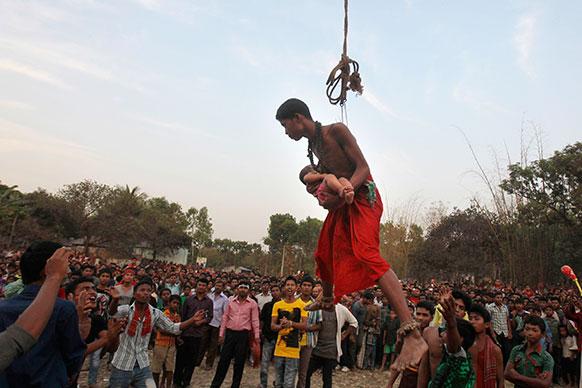 ढाका में चरक पूजा उत्सव के दौरान एक बच्चे को लेकर रस्सी पर चलता एक बांग्लादेशी हिंदू।