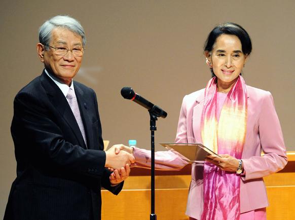 क्योटो विश्वविद्यालय के अध्यक्ष हिरोशी मात्सूमोतो से मानद उपाधि ग्रहण करती म्यांमार की विपक्ष की नेता आंग सान सू ची।