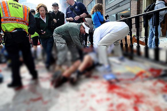 अमेरिका के बोस्टन मैराथन के दौरान हुए बम धमाकों में घायल व्यक्ति को मदद करते लोग।