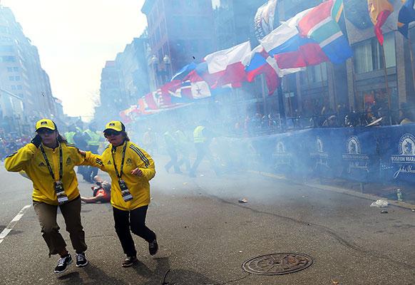 अमेरिका के बोस्टन मैराथन के दौरान हुए बम धमाकों के बाद लोग घटना स्थल से भागते हुए।