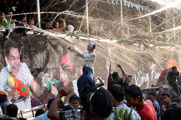म्यामांर में एक परंपरा के दौरान पानी की बौछार करते लोग।