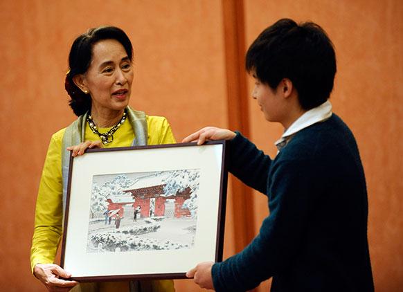 टोक्यो यूनिवर्सिटी के लेक्चरर से तोहफा हासिल करती म्यामांर की विपक्षी नेता आंग सू की।