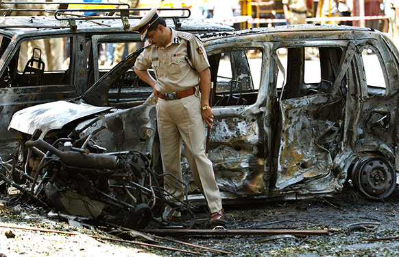 विस्फोट स्थल के पास पुलिसकर्मी जांच करते हुए।