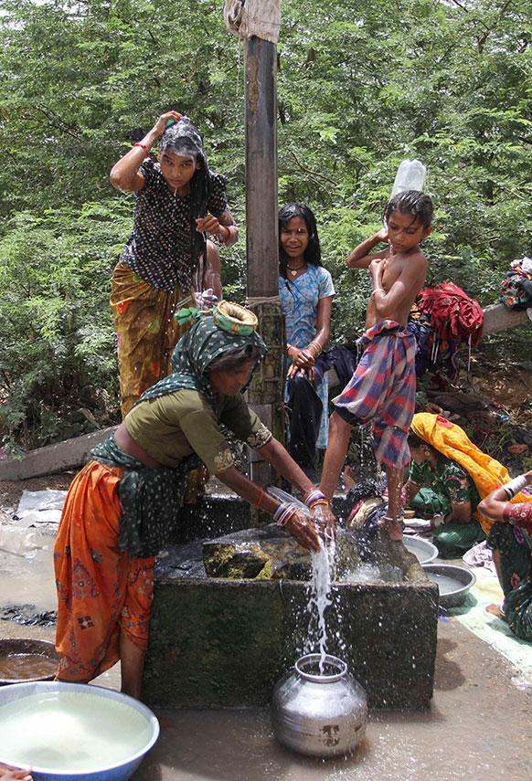 गुजरात के कच्छ जिले में गांधीधाम के बाहरी इलाके में पानी की भारी किल्लत चल रही है। पेयजल आपूर्ति पाइप लाइन से रिस रही पानी को इक्ट्ठा करतीं इलाके की महिलाएं।