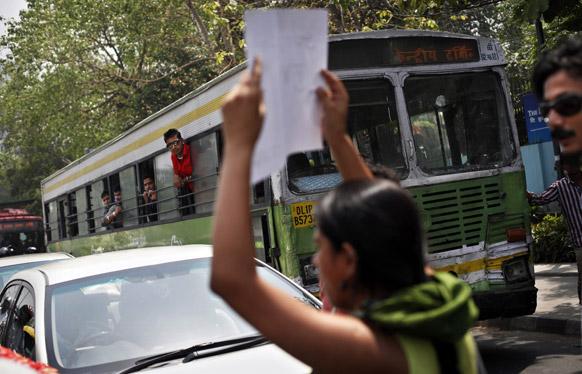दिल्ली पुलिस मुख्यालय के बाहर नारे लिखे तख्ती को लहराती एक लड़की।