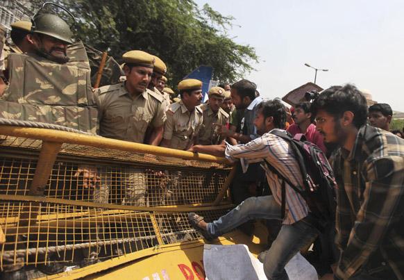 दिल्ली पुलिस मुख्यालय के बाहर लगे बैरिकेड को हटाने का प्रयास करते प्रदर्शनकारी।
