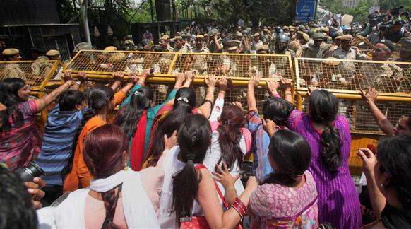 दिल्ली रेप से आक्रोशित महिलाएं दिल्ली पुलिस मुख्यालय में घुसने के लिए बैरिकेड हटाने की कोशिश करती हुईं।