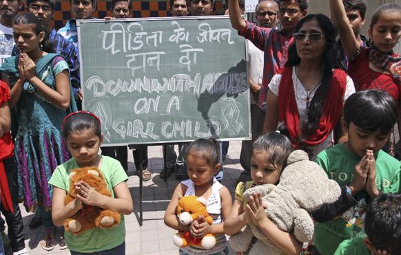 रेप पीड़िता के जल्द ठीक होने के लिए दिल्ली में प्रार्थना करतीं बच्चियां।