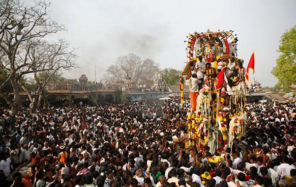 दक्षिण भारतीय राज्य तमिलनाडु में सालाना किन्नर महोत्सव कोवागम के दौरान योद्धा देवता की मूर्ति को रथ में लेकर निकाली गई शोभायात्रा।