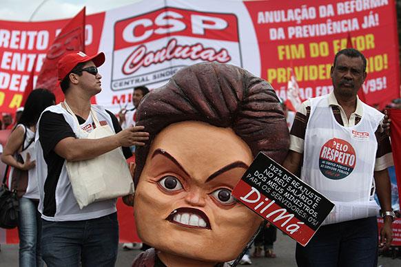 ब्राजील के ब्राजीलिया में मजदूर संगठनों के प्रदर्शन के दौरान ब्राजील की राष्ट्रपति डाइलमा रूसेफ की कठपुतली को हाथ में लिए प्रदर्शनकारी।