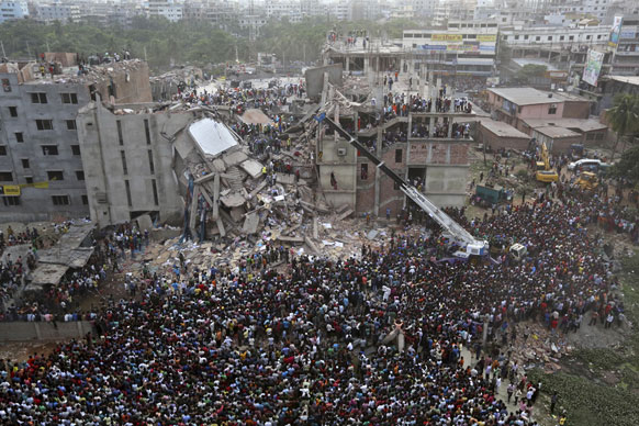 ढाका में जमींदोज इमारत के पास चल रहे राहत एवं बचाव कार्य को देखने भारी संख्या में लोग पहुंच रहे हैं।