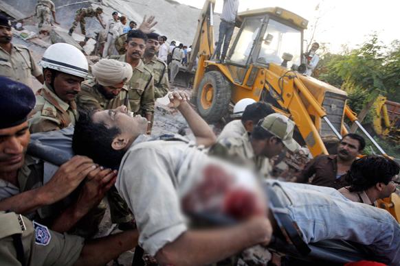 भोपाल में बिल्डिंग गिरने से घायल युवक को अस्पताल ले जाते राहत और बचाव दल।
