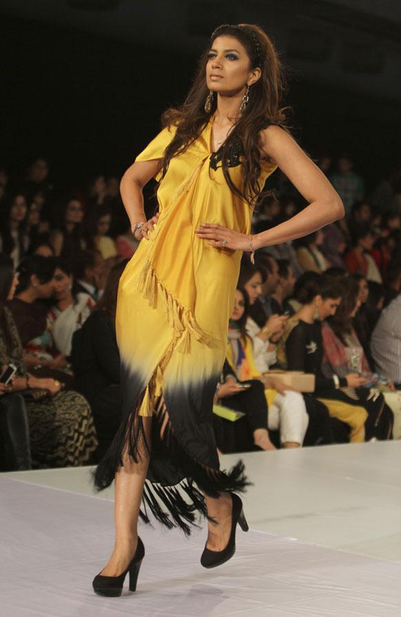 लाहौर फैशन वीक के दौरान डिजायन कपड़े को पेश करती एक मॉडल।