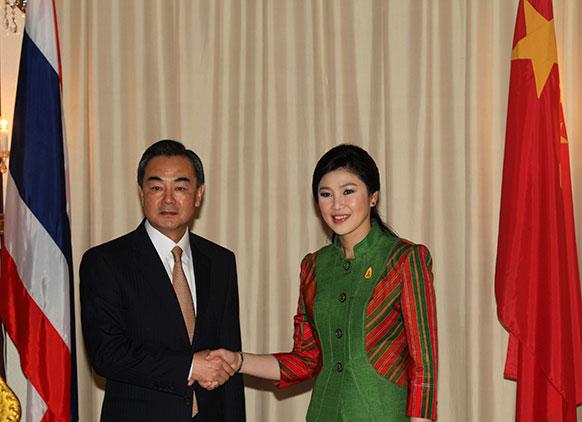 चीनी विदेश मंत्री वांग फी थाइलैंड के प्रधानमंत्री येंगलुक के साथ बैंकाक में मिलती हुई।