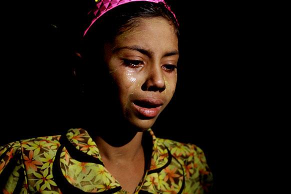 म्यामांर में आंदोलन के बीच रोती एक महिला जहां कई घरों को कुछ लोगों ने जला दिया।