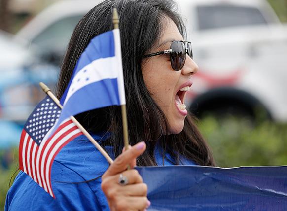 अमेरिका के डोरल में इमीग्रेशन संबंधी प्रदर्शन के दौरान अमेरिकन और होंडुरन झंडे को हाथ में थामे हुए ब्रेंडा बेटनकोर्ट।