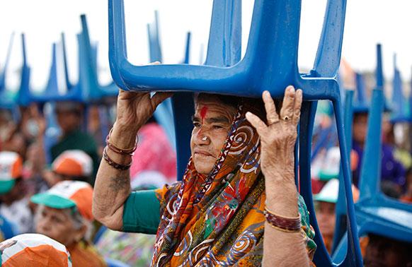 बेंगलुरु में एक चुनाव रैली के दौरान अचानक हुई बारिश से बचने का प्रयास करते कांग्रेस पार्टी के समर्थक और कार्यकर्ता।