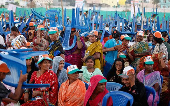 कर्नाटक: बेंगलुरु के बाहरी हिस्से में एक रैली के दौरान प्रधानमंत्री मनमोहन सिंह के भाषण से पहले बारिश से बचने के लिए कुर्सी का सहारा लेते हुए कांग्रेस समर्थक।