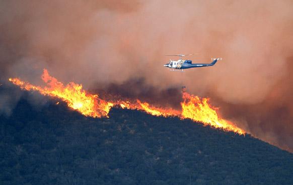 कैलिफ की पहाड़ियों में लगी आग को बुझाने की कोशिश करता एक हेलीकॉप्टर।