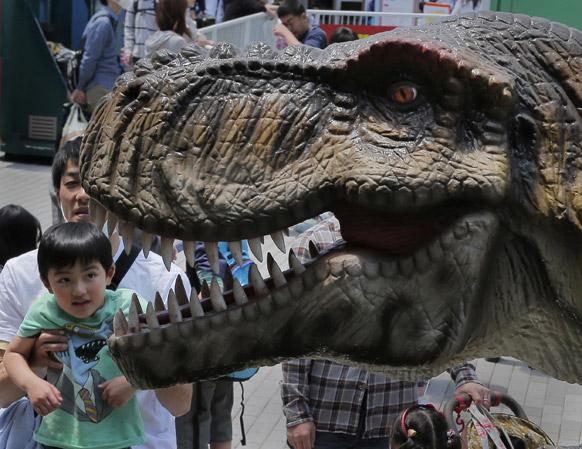 टोक्यो में एक एक्जीबिशन में एक बच्चा 16 फीट के डायनासोर रोबोट को देखते हुए।