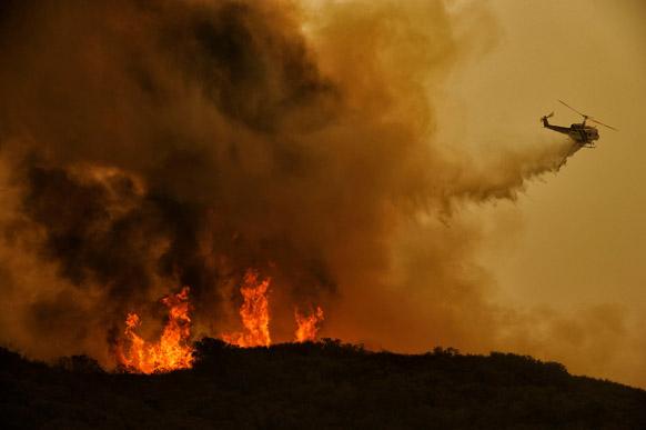 कैलिफ में जंगल में लगी आग बुझाने के लिए हेलीकॉप्टर से पानी छोड़ा गया।
