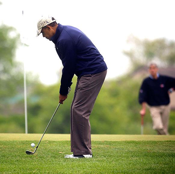 अमेरिकी राष्ट्रपति बराक ओबामा गोल्फ स्टिक के साथ हाथ आजमाते हुए।