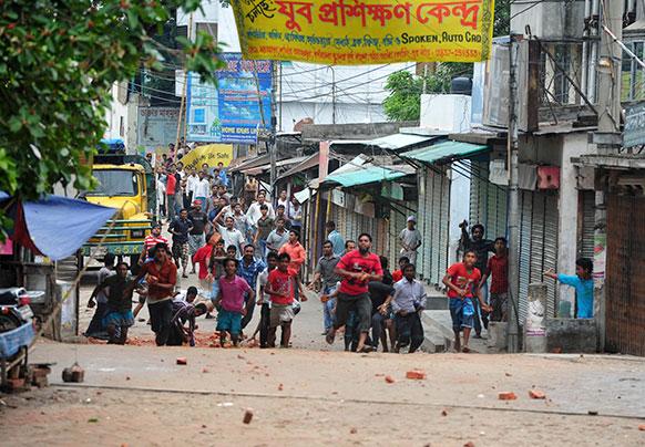 बांग्लादेश की राजधानी ढाका में पुलिस पर पत्थरबाजी करते कुछ युवक।