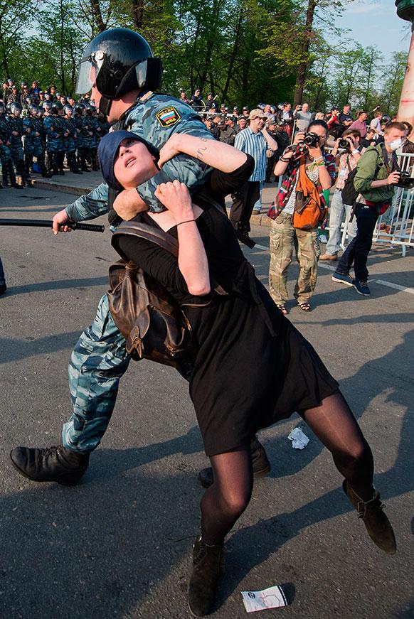 मास्को में एक विरोध-प्रदर्शन के दौरान पुलिसकर्मी एक महिला को ले जाते हुए।