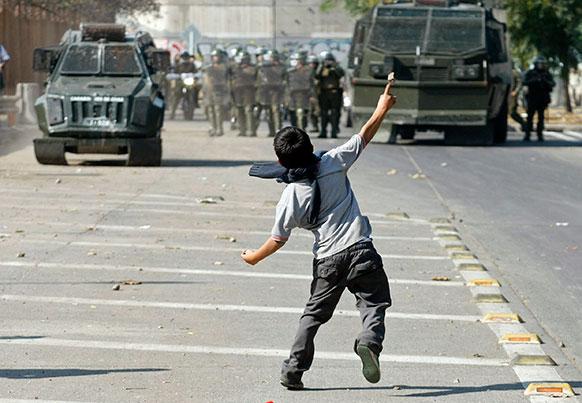 चिली में प्रदर्शन के दौरान पुलिसकर्मियों पर पत्थर फेंकता एक लड़का।