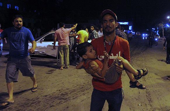 पाकिस्तानी विस्फोट मे घायल एक बच्चे को अस्पताल ले जाते कार्यकर्ता।