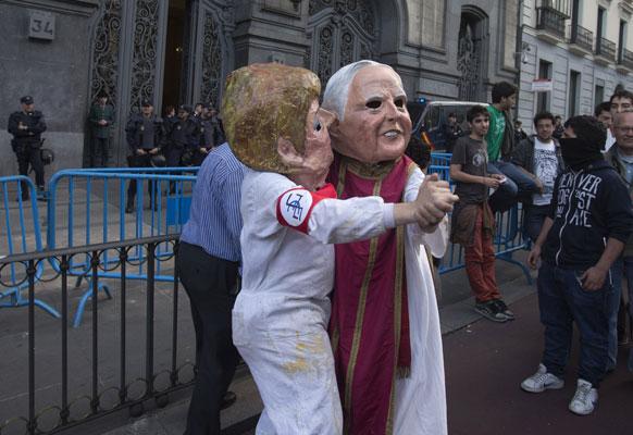स्पेन में मास्क पहनकर विरोध-प्रदर्शन करते लोग।