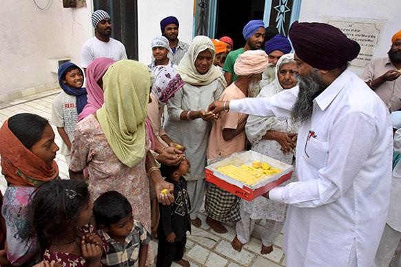 पाक चुनाव में नवाज शरीफ की जीत की खुशी में अमृतसर के निकट स्थित उनके गांव जाति उमरा में मिठाइयां बांटते ग्रामीण।