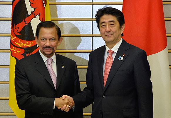 टोक्यो में जापानी प्रधानमंत्री शिंजो एबे से हाथ मिलाते हुए ब्रूनोई के सुल्तान हसनल बोलकिया।