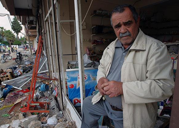 टर्की बॉर्डर के निकट रेहनेली में एक ब्लास्ट में क्षतिग्रस्त अपनी दुकान को निहारता हुआ अता इल्दिज।
