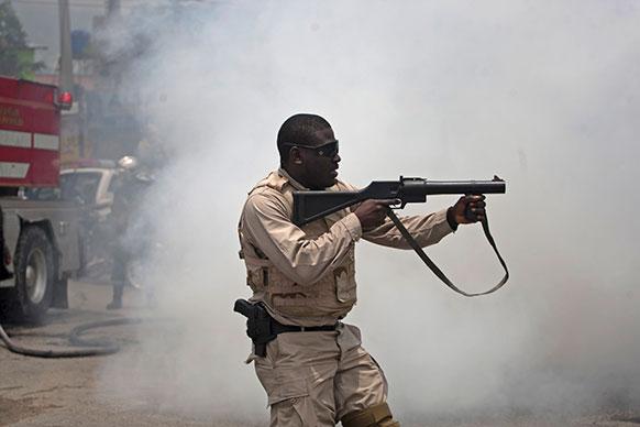 हैती में भड़के दंगे के दौरान भीड़ पर फायरिंग करता पुलिसकर्मी।