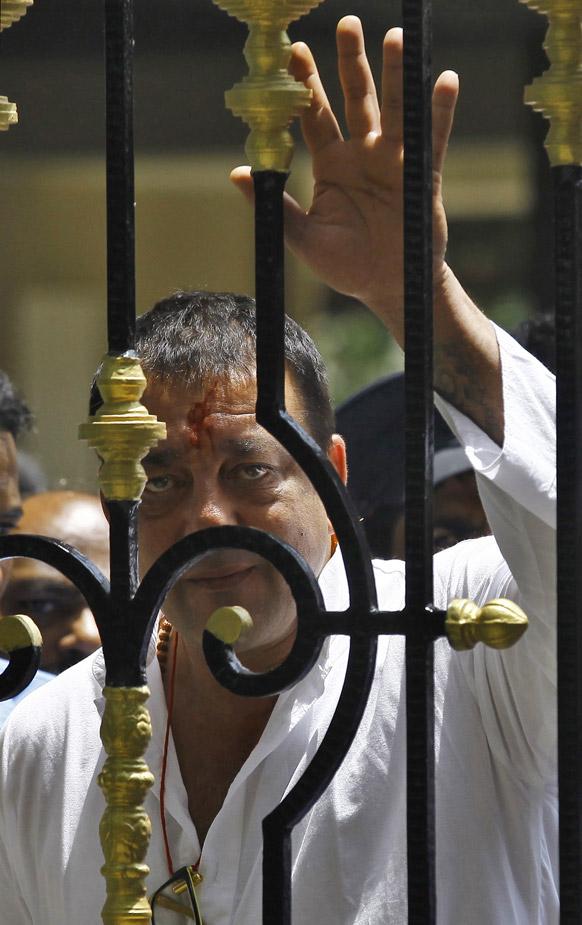 सरेंडर करने जाने से पहले मुंबई स्थित अपने घर के बाहर समर्थकों का हाथ हिलाकर अभिवादन करते संजय दत्त।