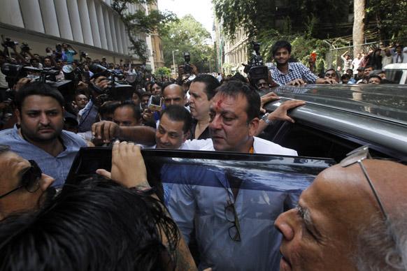 कोर्ट में सरेंडर करने के लिए पहुंचे संजय दत्त अपने कार से बाहर निकलते हुए।
